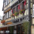 a beautiful house with red geraniums cascading from flower boxes in Town of Obernai in France