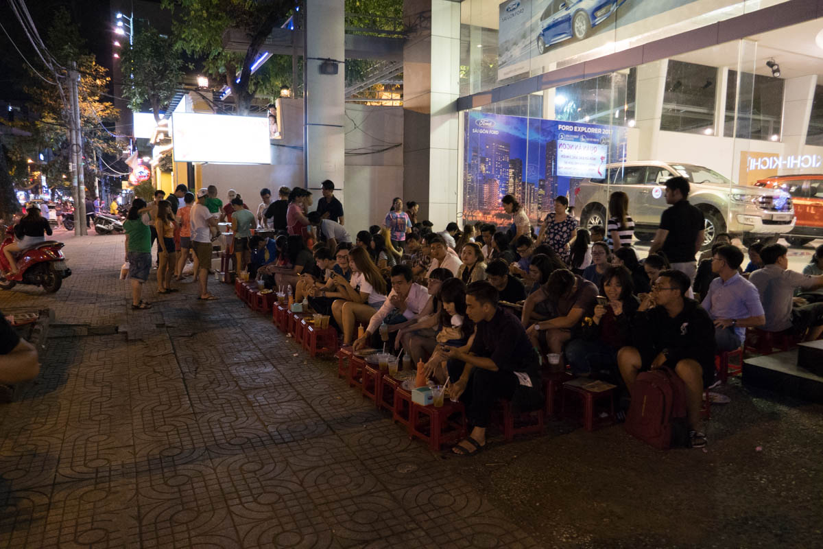 people eating at the sidewalk on the saigon street food tour